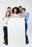 Gelukkige vriendschappelijke groep jonge vrienden met een teken Stock Fotografie