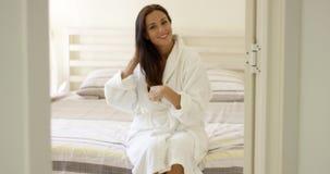 Gelukkige vriendschappelijke jonge vrouw in een witte badrobe stock video