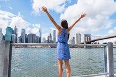Gelukkige vrijheidsvrouw die bij de stad van NYC New York stedelijke horizon toejuichen royalty-vrije stock afbeelding