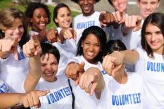 Gelukkige vrijwilligersgroep die naar camera richt