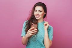 Gelukkige vrolijke blije vrouw met lange haar naakte make-up in status binnen met haar smartphone die met vrienden of vriend babb Royalty-vrije Stock Afbeelding