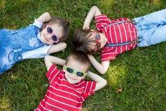 Gelukkige vrolijke glimlachende kinderen, die op een gras, gezongen dragen leggen stock foto