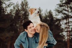 Gelukkige vrolijke glimlachende mens met meisje en hond op zijn rug kussend paar van jongeren in denimkostuums in sneeuwbos royalty-vrije stock fotografie