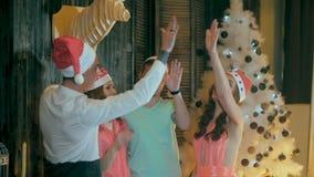 Gelukkige, vrolijke groep vrienden bij Kerstmispartij Groet in camera, die pret het glimlachen het vieren nieuwe jaar` s vooravon stock video