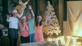 Gelukkige, vrolijke groep vrienden bij Kerstmispartij Groet in camera, die pret het glimlachen het vieren nieuwe jaar` s vooravon stock footage