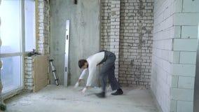 Gelukkige vrolijke jonge bouwer die bij bouwwerf dansen stock videobeelden