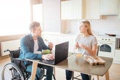Gelukkige vrolijke jonge student die met handicap en inclusiviteit salade en het bestuderen eten Hij bekijkt vrouw en glimlach stock afbeelding