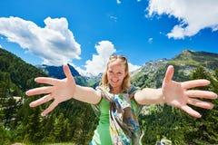 Gelukkige vrolijke jonge vrouw die voor blauwe hemel en het mountainsembracing omhelzen stock afbeelding