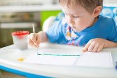 Gelukkige vrolijke kindtekening met borstel in album dat heel wat het schilderen hulpmiddelen met behulp van Het concept van de c Royalty-vrije Stock Foto