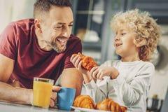 Gelukkige vrolijke mens en jongen die croissant eten royalty-vrije stock foto
