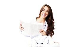 Gelukkige vrouw in bed met een krant royalty-vrije stock afbeeldingen