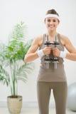 Gelukkige vrouw in de domoren van de sportkledingsholding Stock Foto's