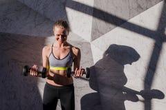 Gelukkige vrouw in de domoren van de sportkledingsholding Stock Afbeeldingen
