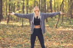 Gelukkige vrouw in de herfst met uitgestrekte wapens stock afbeelding