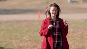 Gelukkige vrouw in de herfstpark Blije en opgewekte jonge vrouw die pret hebben die gele bladeren in het zonnige dalingspark werp stock footage