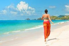 Gelukkige vrouw in de zomer losse broeken die op tropisch strand lopen stock foto's