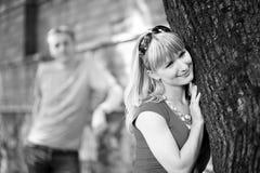 Gelukkige vrouw dichtbij boom en haar boyfrend Stock Afbeelding