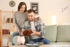 Gelukkige vrouw dichtbij echtgenoot met salaris binnen De besparingenconcept van het geld royalty-vrije stock fotografie