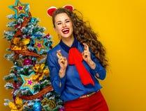 Gelukkige in vrouw dichtbij Kerstboom met gekruiste vingers Royalty-vrije Stock Foto's