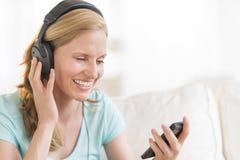 Gelukkige Vrouw die aan Muziek door Hoofdtelefoons luisteren Royalty-vrije Stock Foto's