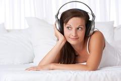 Gelukkige vrouw die aan muziek luistert die op bank ligt Royalty-vrije Stock Afbeeldingen