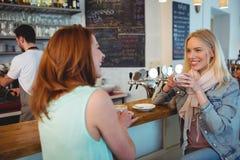 Gelukkige vrouw die aan vriend bij koffieteller spreekt stock fotografie
