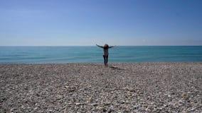 Gelukkige vrouw die aan water loopt dat wapens opheft, die pret hebben tijdens de zomervakantie stock video