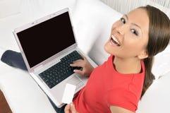 Gelukkige vrouw die achterwaarts met laptop kijkt Royalty-vrije Stock Foto