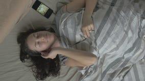 Gelukkige vrouw die in bed met hoofdtelefoons aan muziek in de ochtend luisteren De mening vanaf de bovenkant stock footage