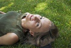 Gelukkige vrouw die bij gras het glimlachen leggen stock afbeeldingen