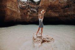 Gelukkige vrouw die bij het rotsstrand genieten van Het concept van de zomervakanties royalty-vrije stock afbeelding