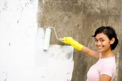 Gelukkige vrouw die buitenmuur schildert Royalty-vrije Stock Foto