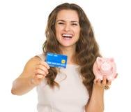 Gelukkige vrouw die creditcard en spaarvarken tonen Royalty-vrije Stock Fotografie