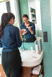 Gelukkige vrouw die de borstelbadkamers gebruiken van de poedersamenstelling Royalty-vrije Stock Fotografie