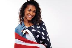 Gelukkige vrouw die de vlag van de V.S. op haar schouders dragen Royalty-vrije Stock Fotografie