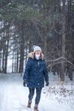 gelukkige vrouw die in de winterhout lopen die omhoog sneeuw het vallen bekijken stock afbeeldingen