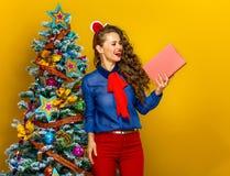 Gelukkige in vrouw die dichtbij Kerstboom boek bekijken Royalty-vrije Stock Fotografie