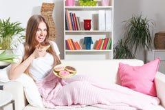 Gelukkige vrouw die donuts eten stock foto's