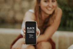 Gelukkige vrouw die door mobiele telefoon met bij Black Friday-verkoop winkelen royalty-vrije stock fotografie