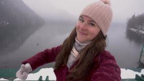 Gelukkige vrouw die duim tonen bij Ritsa-meer in Abchazië Sneeuwdag in de winter stock footage