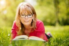 Gelukkige vrouw die een boek lezen tijdens de lente in aard Stock Foto