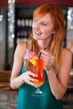 Gelukkige vrouw die een cocktailglas houden bij barteller Royalty-vrije Stock Fotografie