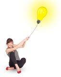 Gelukkige vrouw die een gloeilampenballon houden Stock Afbeelding
