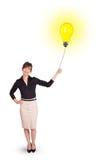 Gelukkige vrouw die een gloeilampenballon houden Stock Foto