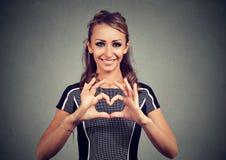Gelukkige vrouw die een hart met haar handen maken stock foto