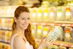 Gelukkige vrouw die in een kruidenierswinkelopslag winkelen Royalty-vrije Stock Fotografie