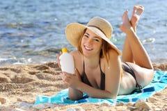 Gelukkige vrouw die een lotion van de zonneschermfles op het strand houden Stock Afbeeldingen