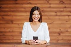 Gelukkige vrouw die een slimme telefoon in de straat met behulp van stock afbeeldingen