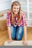 Gelukkige vrouw die een tapijt uit rolt Royalty-vrije Stock Foto's