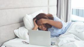 Gelukkige vrouw die een videopraatje hebben terwijl thuis het liggen op bed stock videobeelden